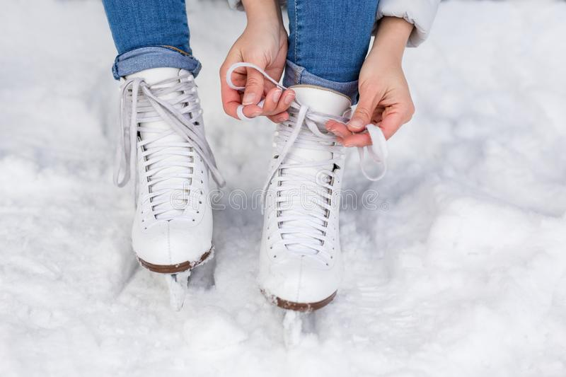 Female hands tying white skates on the ice area at rink royalty free stock images