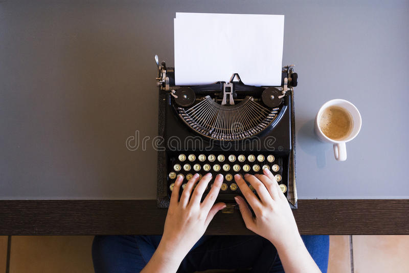 Close up of female hands typing on retro typewriter. Cup of coffee is at right side.Indoors. Top view. stock photos