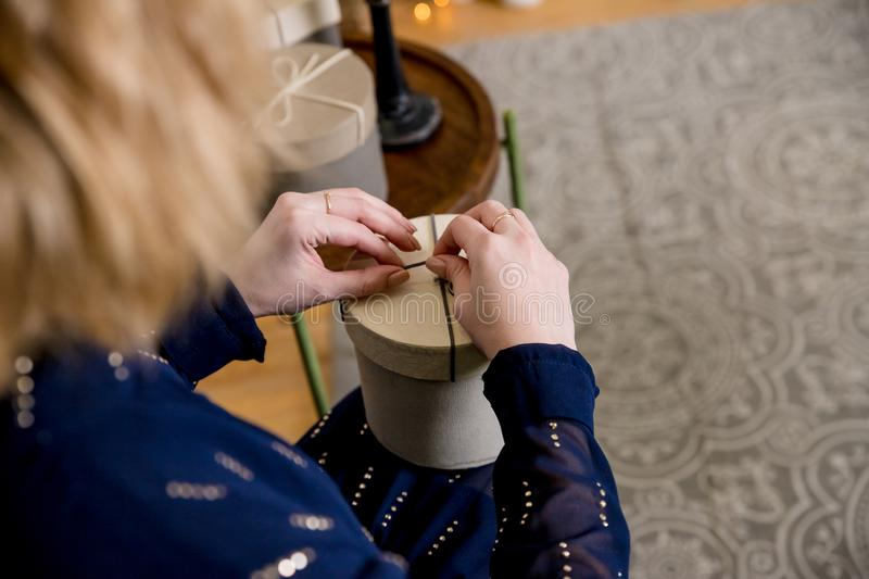Close-up of female hands unpacking a present.Copy space.Female hands opening gift box, copy space. Christmas, hew year. Close-up of female hands unpacking a royalty free stock image
