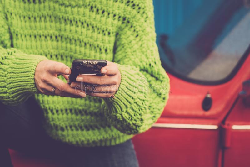 Close-up female hands using and messaging with modern technology smart phone - green jackets and red old vintage car in background stock images