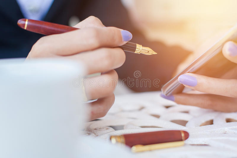 Close-up of female hands using modern smart phone while working stock photography