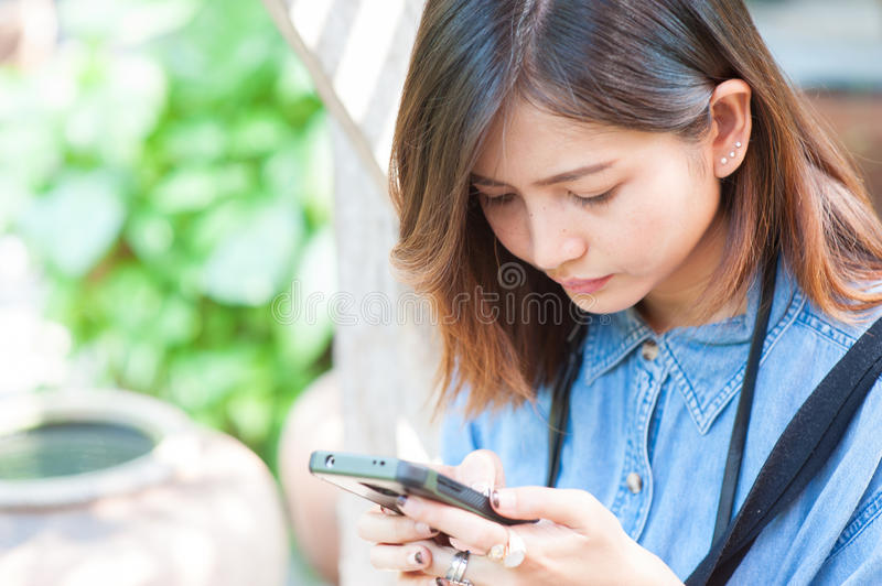 Close-up of female hands using modern smart phone while working,Young woman using a touchscreen smartphone. With copy space stock images