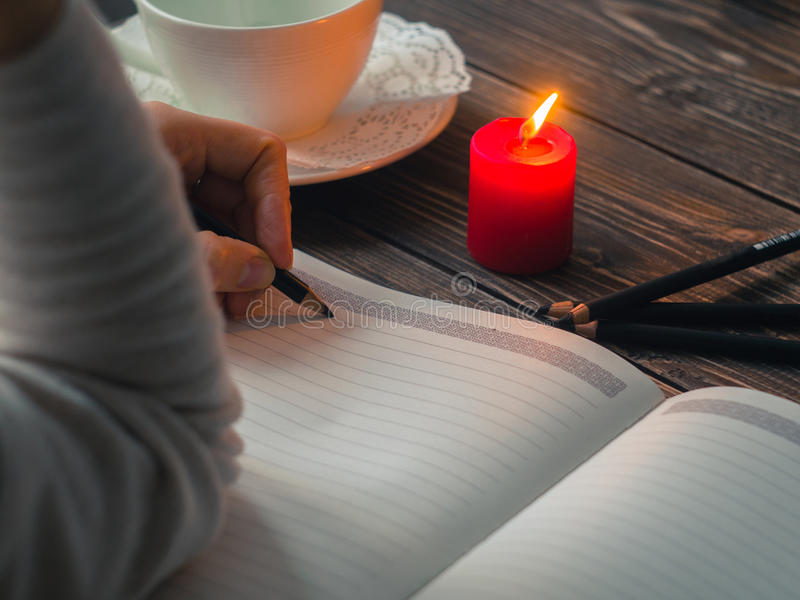 Close up of female hands writing with pencil at cafe with burning candle stock image