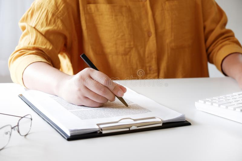 Close-up of female hands. writing something in her office. royalty free stock image