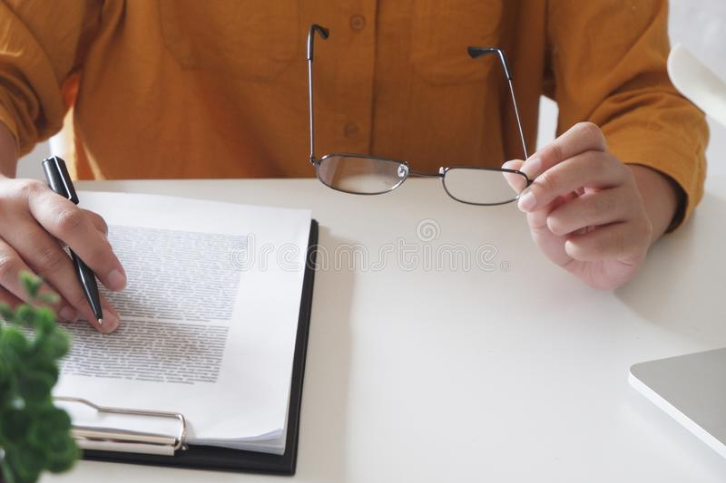 Close-up of female hands. writing something and holding glasses in her office stock photos