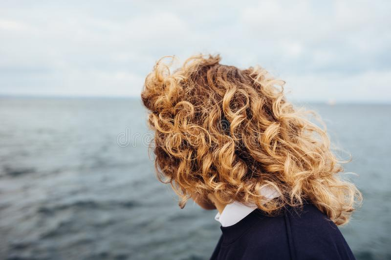 Close-up female head with fluttering red curly hair royalty free stock images