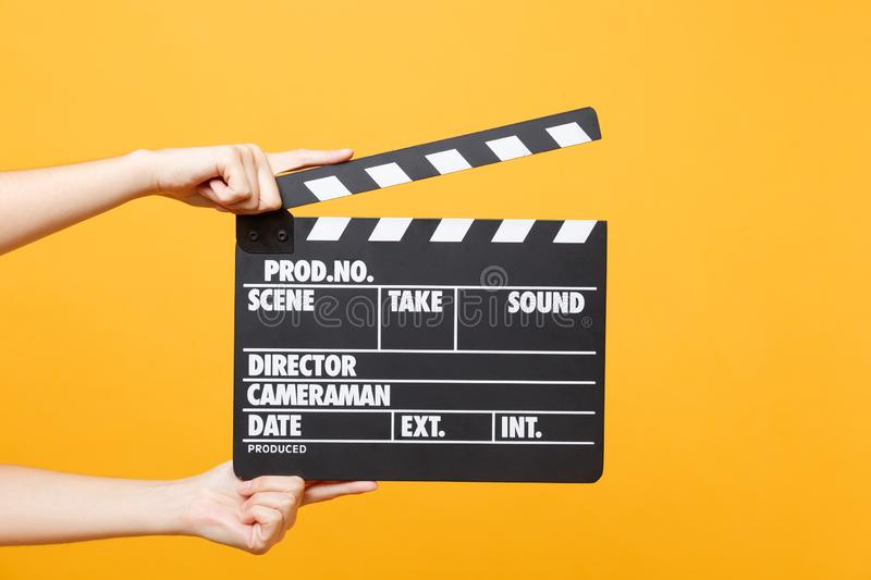 Close up female holding in hand classic director clear empty black film making clapperboard isolated on trending yellow. Close up female holding in hand classic royalty free stock image