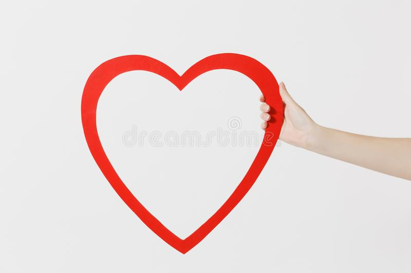 Close up female holds in hand big red heart isolated on white background. Copy space for advertisement. With place for stock photos