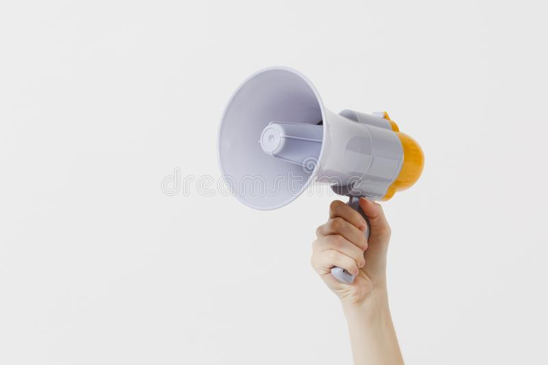 Close up female holds in hand bullhorn public address megaphone isolated on white background. Hot news, announce. Discounts sale, communication concept. Copy stock photo