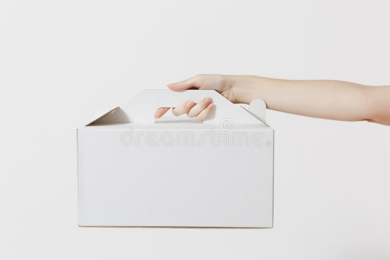 Close up female holds in hand cake dessert in unmarked clear empty blank cardboard box, food order isolated on white. Background. Delivery concept. Copy space stock photo