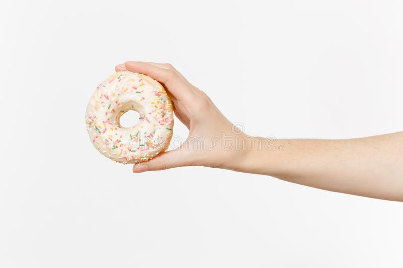 Close up female holds in hand colorful white donut isolated on white background. Proper nutrition or sweets, dessert. Fast food, dieting morning concept. Copy royalty free stock photography