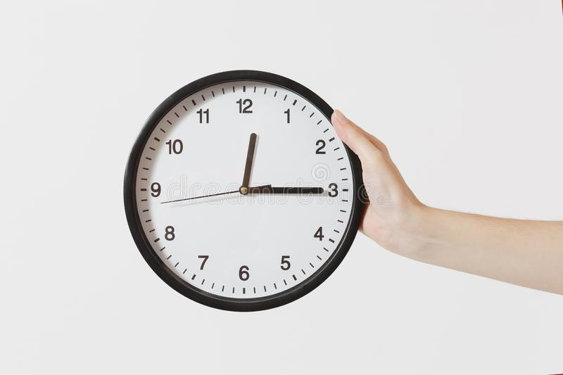 Close up female holds in hand round black and white clock isolated on white background. Time concept. Time is running stock photos