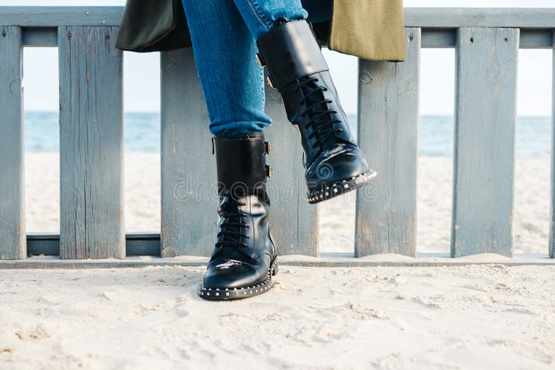 Close-up of female legs in black boots and jeans stock photo
