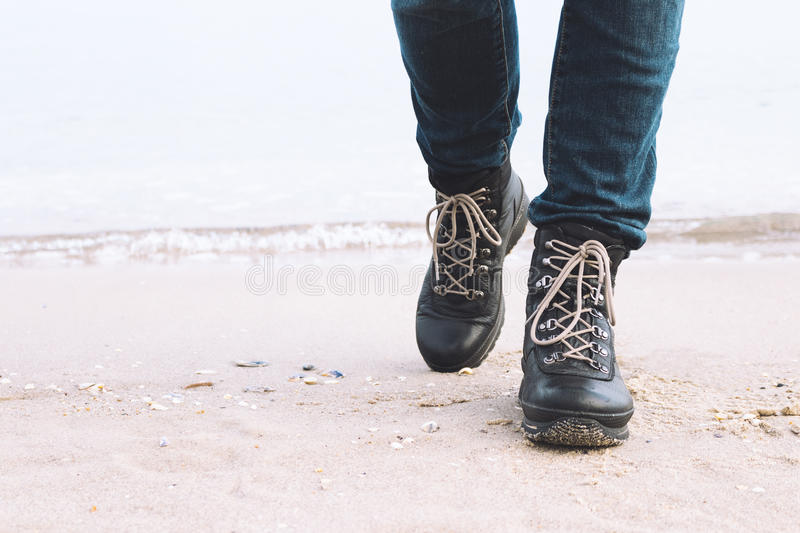 Close-up of female legs in the winter boots are on the beach royalty free stock image