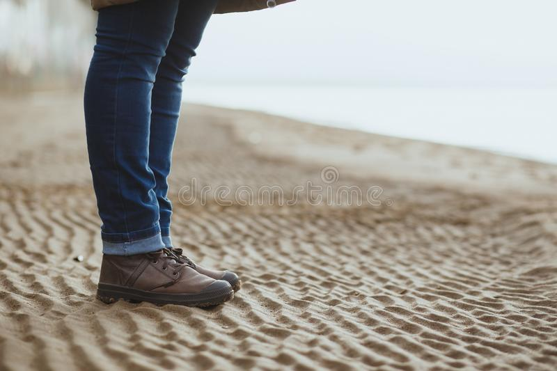 Close-up of female legs in the winter boots are on the wet beach, fall or winter time. Copy space stock image
