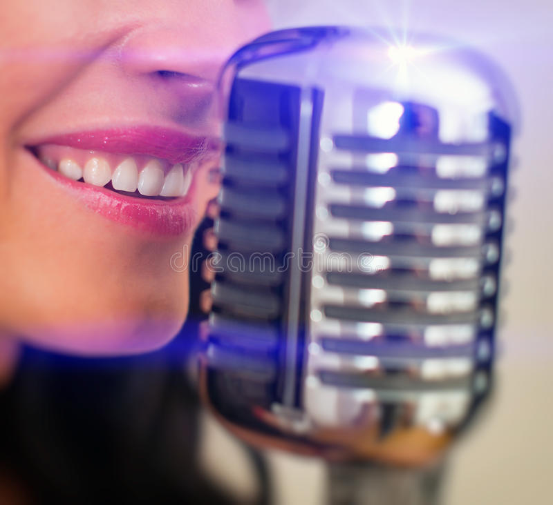Close-up of female mouth singing. Close-up of female mouth singing into vintage microphone stock images