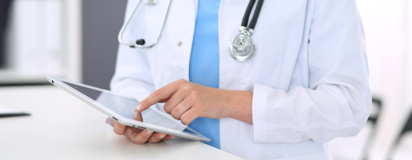 Unknown doctor woman at work. Female physician using digital tablet while standing near reception desk at clinic or. Close-up of female physician using digital royalty free stock images