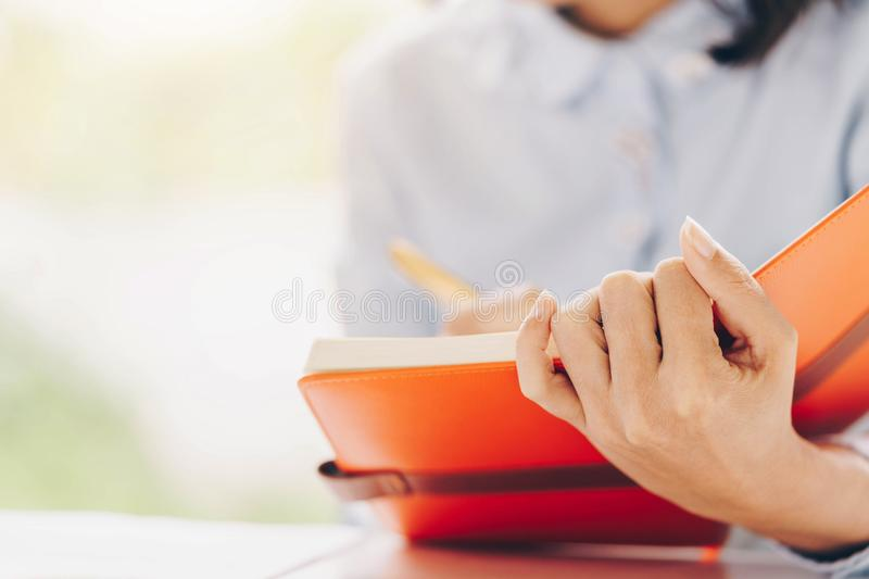 Close-up of female or Secretary hands making notes during discus stock image
