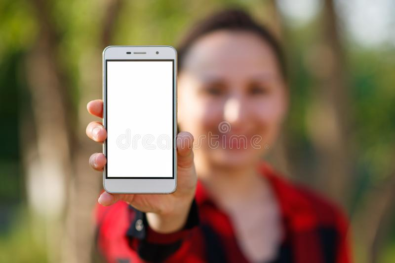 Close up of a female showing a blank vertical phone screen on the street royalty free stock image