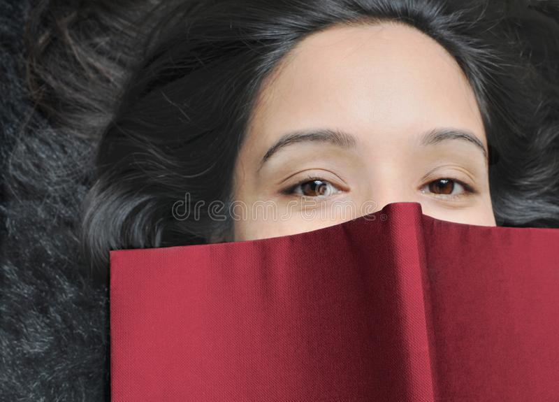 Close up of a female student. Indian Girl covering her face with a book stock photo