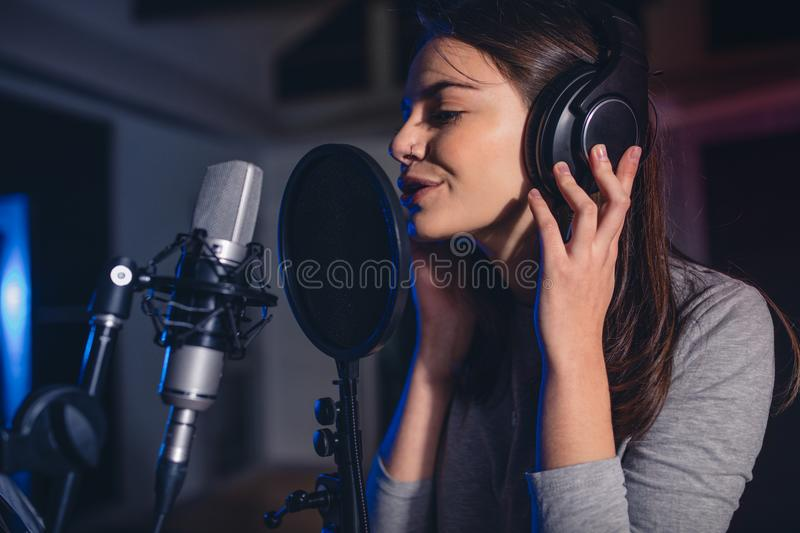 Female vocal artist singing in a recording studio stock images