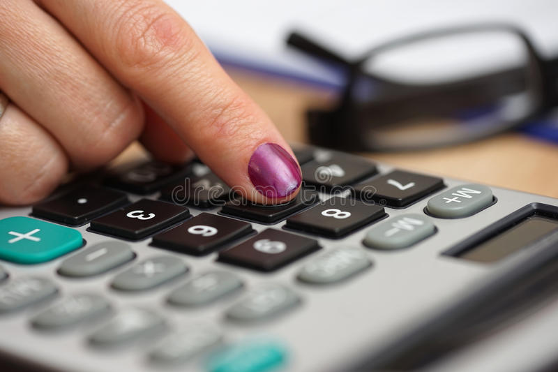close up of a female woman pressing on calculator button with eyeglasses and paperwork in background. accounting and bookkeeping stock photo