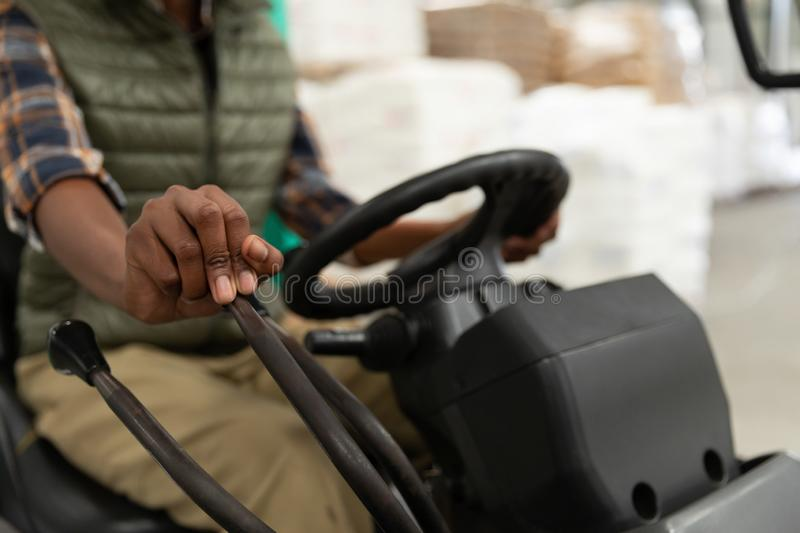 Female worker driving forklift in warehouse. Close-up of female worker driving forklift in warehouse. This is a freight transportation and distribution warehouse stock photo