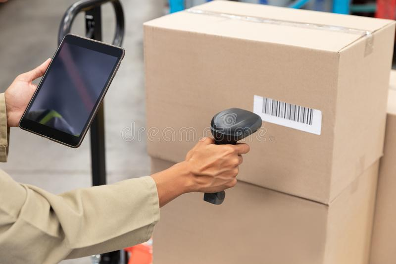 Female worker scanning package with barcode scanner while using digital tablet in warehouse. Close-up of female worker scanning package with barcode scanner royalty free stock photo
