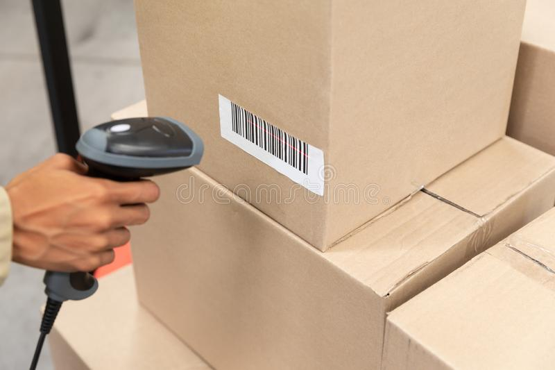 Female worker scanning package with barcode scanner in warehouse. Close-up of female worker scanning package with barcode scanner in warehouse. This is a freight stock photography