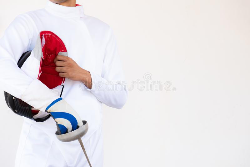 Close-up of a fencer in white fencing suit and holding his mask royalty free stock photo