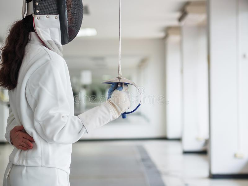 Close-up of a fencer in white fencing suit and holding a sword o stock photography