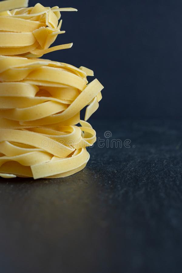 Close-up of fettuccine pasta stacked vertically on black background. With copy space royalty free stock image