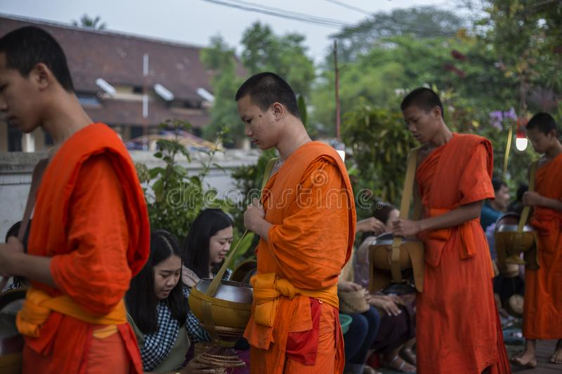 Alms giving ceremony in Luang Prabang, Laos. Close-up of few young Buddhist monks who collect alms from people giving on the street early in the morning in Luang royalty free stock images