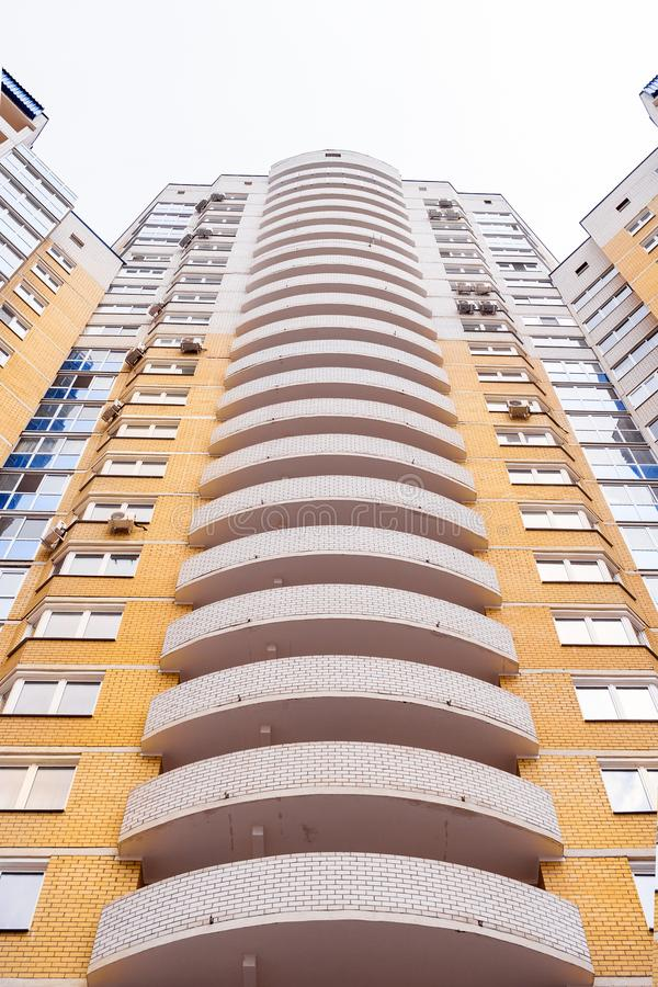 Close-up figured convex balconies of multi-storey yellow modern brick residential building. royalty free stock photos