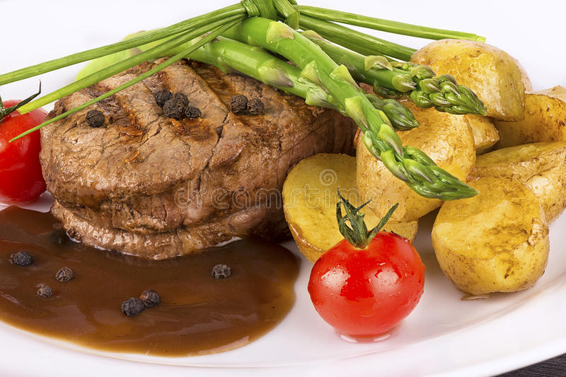 Close up on fillet mignon. With vegetables on the side royalty free stock photos