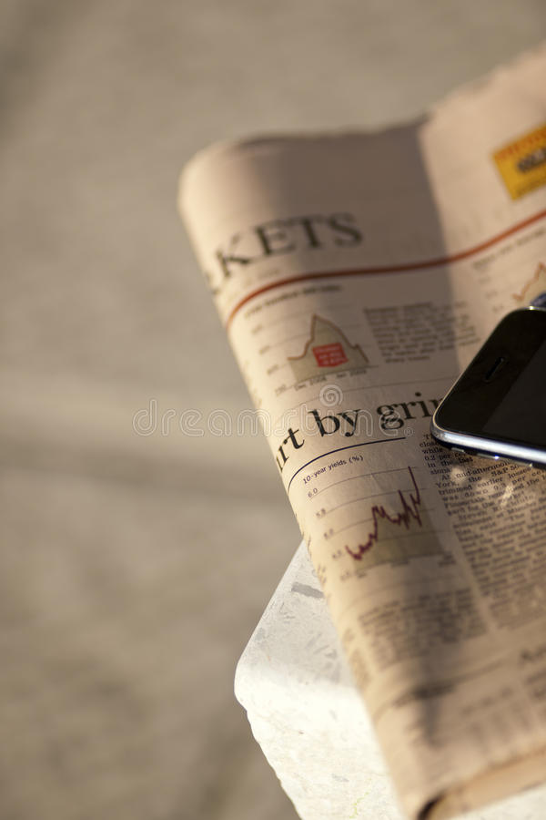 Close-up of financial newspaper and mobile phone stock photography