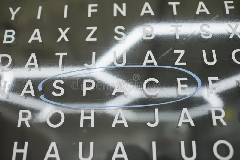 Finding words with letters. Close-up of finding word game with English letters on board, space word circled in blue stock image