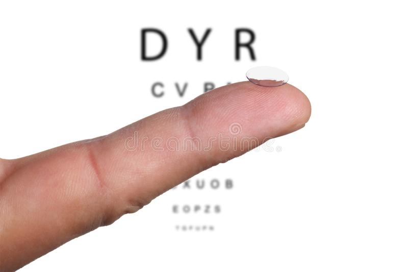 Close up on a finger holding a contact lens and a eye chart on the background stock image