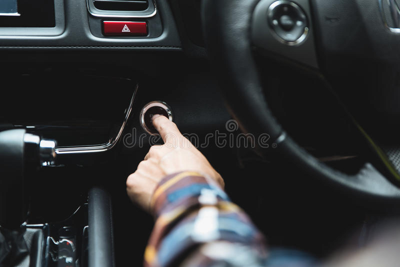 Close up Finger press button functions car engine start and stop. In motor vehicle for pre start checklist concept stock photography