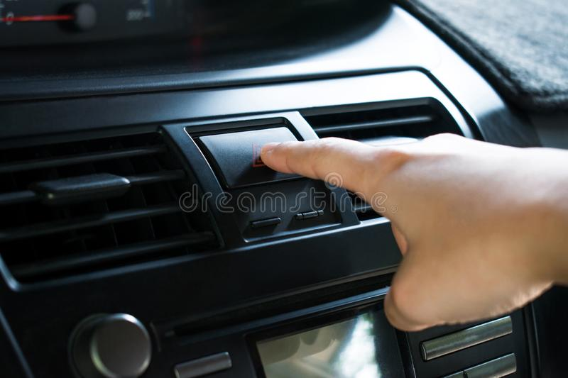 Close-up, Finger touch the emergency button on the car dashboard.  royalty free stock image