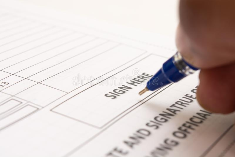 Close up of Fingers holding a pen and signing a income tax form. royalty free stock photo