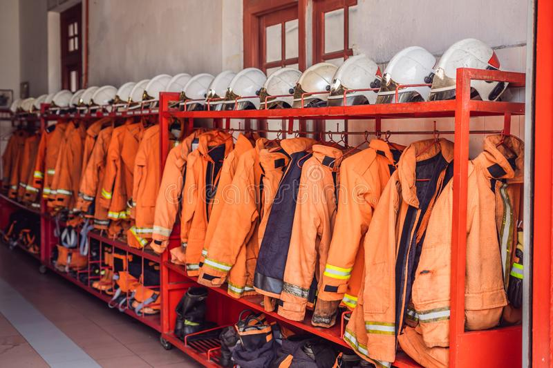 Close up of Fireman coats, helmets and boots wait for the next call. Dressing room of the volunteer fire department stock image