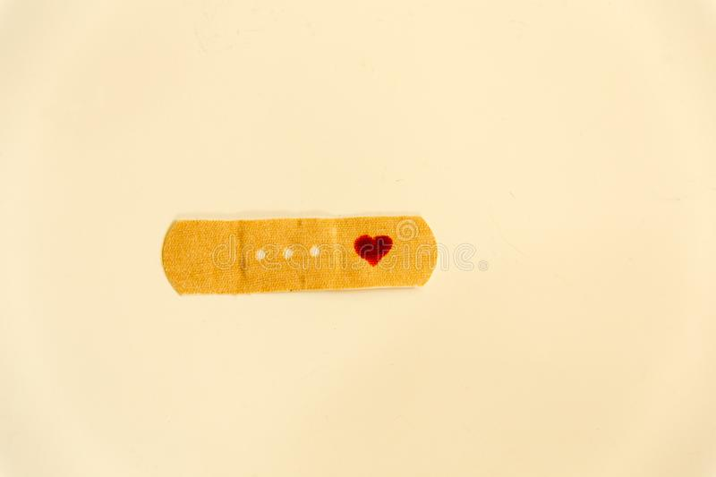 Close up of a first aid band with hand drawn red heart. Broken heart and healing love concepts royalty free stock images