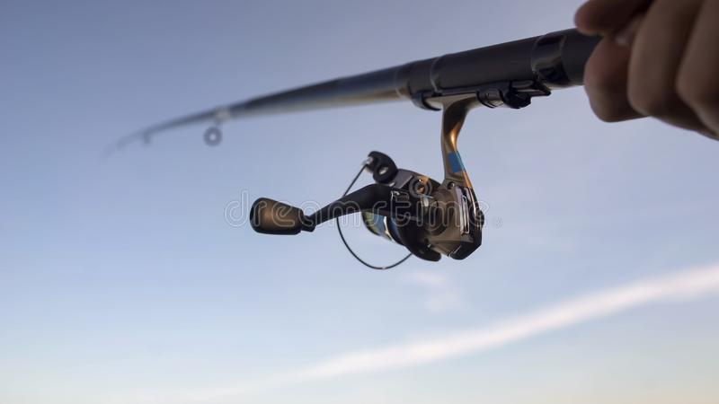 Close up of fishing reel, man catching fish with spinning rod in hand, gear royalty free stock photo