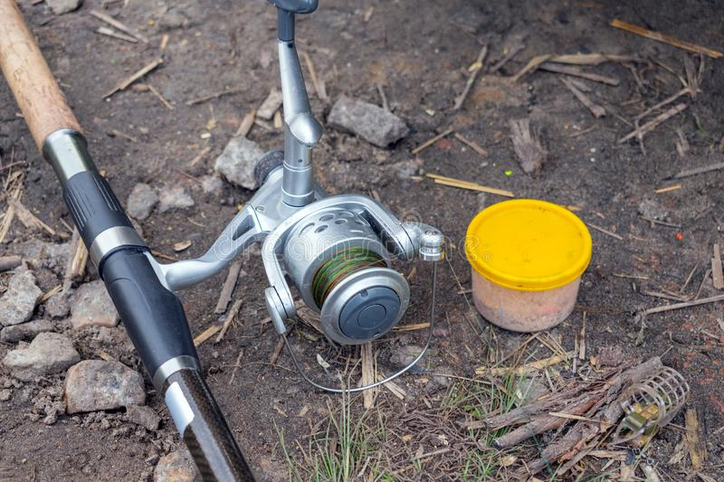 Close up Fishing rod feeder and box on the river bank. Fisherman royalty free stock photos