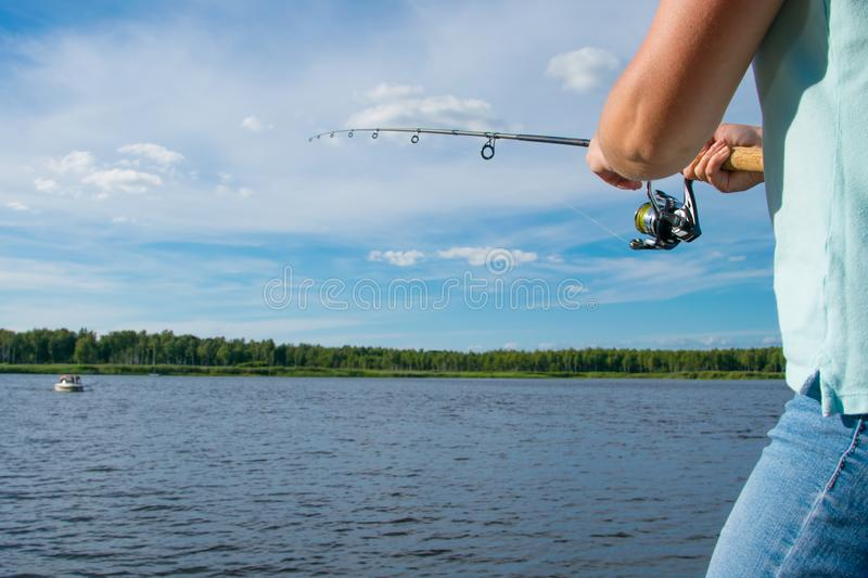 Close up, fishing on spinning, against the blue sky and lake, there are places for an inscription royalty free stock photos