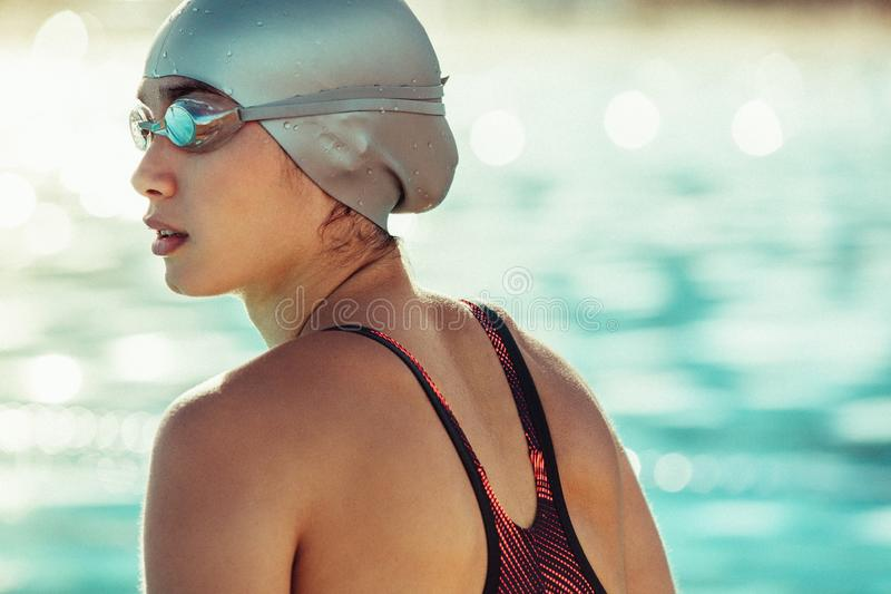 Professional swimmer looking away. Close up of fit young female swimmer in swim cap and goggles looking away. Professional swimming athlete in swimwear royalty free stock image