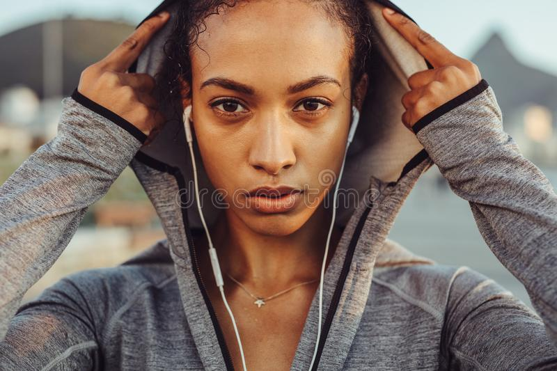 Confident female runner in a hoodie stock photography