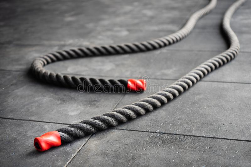 Close up of fitness battle ropes lie on black floor in fitness gym. Sport and fitness equipment. Functional training stock images