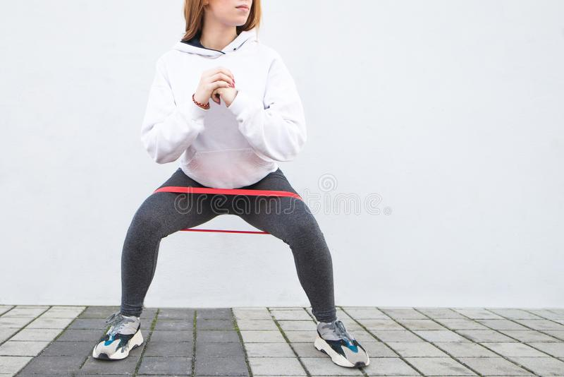 Close-up fitness girl squats with a rubber band on a white background. Enjoy sports on the street. Warm up before running. Copyspace stock images
